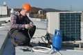 Young repairman on the roof fixing air conditioning system model is actual electrician Stock Photos
