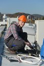 Young repairman on the roof fixing air conditioning system model is actual electrician Royalty Free Stock Image