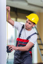 The young repairman with tape measure working on repairs Royalty Free Stock Photo