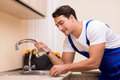 The young repairman working at the kitchen Royalty Free Stock Photo