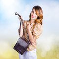 Young retro fashion model holding leather handbag cute clutch bag with hand to chest love of accessorys Royalty Free Stock Images
