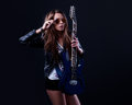 Young rockstar woman with blue electric guitar Royalty Free Stock Photo