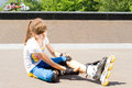 Young roller skater rubbing her calf muscle female teenage sitting on the tarmac to relieve a cramp or strain sustained Stock Images