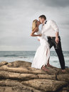 Young romantic couple dancing on beach rocks with champagne and kissing Royalty Free Stock Images