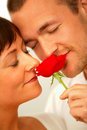 A young romantic couple enjoying the scent of a rose Royalty Free Stock Photo