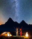 Young romantic couple - guy and girl raised their hands up under the stars near campfire and tent Royalty Free Stock Photo