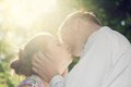 Young romantic couple kissing in sunshine vintage love with dating romance flare Stock Image