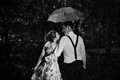 Young romantic couple in love flirting in rain. Black and white Royalty Free Stock Photo