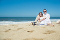 Young romantic couple sitting on the beach
