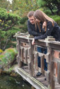 Young romantic couple standing on the bridge looking on the wate Royalty Free Stock Photo
