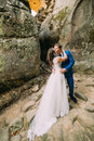 Young and romantic newlywed couple kissing in weathered rock cleft Stock Photos
