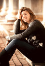 Young romantic woman in black sweater sitting on street Stock Photography