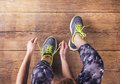 Young runner tying her shoes unrecognizable shoelaces studio shot on wooden floor background Stock Photo