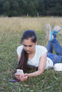 Young sad beautiful woman texting message on mobile phone in urban park - Teenager model girl with worried facial expression hold Royalty Free Stock Photo