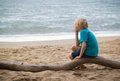 Young sad boy thinking on the beach portrait of a sitting a log with copy space Royalty Free Stock Photo