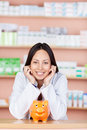 Young saleswoman in drug store with piggy bank leaning head on Royalty Free Stock Image
