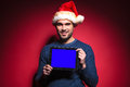 Young santa man holding a blue screen tablet pad computer