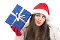 Young santa woman wondering what is in the blue gift box cute brunette caucasian with hat looking sideways making facial Stock Photography