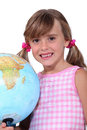 Young schoolgir schoolgirl with a large globe Royalty Free Stock Photo