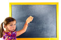 A young schoolgirl erase the blackboard with pigtails Stock Photo