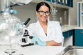 Young scientist in eyeglasses working with microscope and smiling at camera in chemical lab Royalty Free Stock Photo