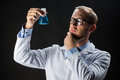 Young scientist holding test flask with chemical Royalty Free Stock Photo