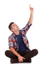 Young seated man pointing up Royalty Free Stock Photo