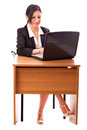 Young secretary at her desk pretty with black suit sitting in front of a laptop Royalty Free Stock Photo