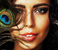 Young sensitive brunette woman with peacock feather eyes close u Royalty Free Stock Photo