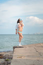 Young sensual lady in swimwear standing on rock sunglasses and white trainers exposing her perfect body to the sun summer day Royalty Free Stock Photo