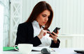 Young serious businesswoman typing on her smartphone in office Stock Photography