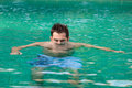Young serious man in swimming pool looking from water the Stock Images