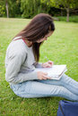 Young serious woman sitting in a park while writing on a noteboo Royalty Free Stock Photos