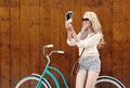 Young sexy blond woman standing near a green vintage bicycle holding photos and smiling warm tonning supersexy Royalty Free Stock Images
