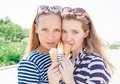 Young sexy blonde best friends girls eating ice cream in summer hot weather in sunglasses have fun and good mood looking in camera Royalty Free Stock Photo