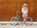 Young sexy blonde girl with long hair with brown vintage bag in sunglasses standing near vintage green bicycle and holding a cup o