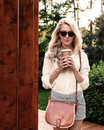 Young sexy blonde girl with long hair in sunglasses with brown vintage bag holding a cup of coffee have fun and good mood looking Royalty Free Stock Photo