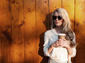 Young sexy blonde girl with long hair in sunglasses holding a cup of coffee have fun evening soft sunlight, warm, tonning Royalty Free Stock Photo