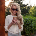 Young sexy blonde girl with long hair in sunglasses holding a cup of coffee have fun and good mood looking in camera and smiling, Royalty Free Stock Photo