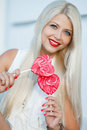 Young sexy blonde woman with heart shaped lollipop portrait of a glamourous beautiful holding Royalty Free Stock Photography