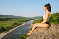 Young sexy brunette girl with muscular body relaxing outdoor in beautiful mountains landscape. Meditation and Relax. Royalty Free Stock Photo