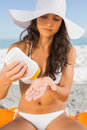Young sexy brunette with straw hat putting on sun cream the beach Royalty Free Stock Image