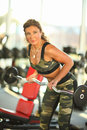 Young brunette woman gym doing biceps exercise with barbell. Royalty Free Stock Photo
