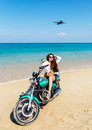 Young sexy girl in a bathing suit on a beach with the motorcycle Royalty Free Stock Photo