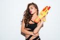 Young sexy girl holding water gun and posing in bikini Royalty Free Stock Photo