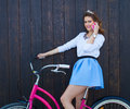 Young sexy girl with long hair with pink phone standing near vintage pink bicycle and speaking on the phone, have fun and good moo Royalty Free Stock Photo