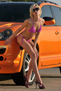 Young sexy girl posing by metallic orange sport car Stock Photography