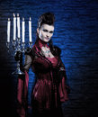 A young and sexy lady vampire holding candles Royalty Free Stock Photo