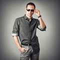 Young sexy man wearing shirt and sunglasses fashion portrait of poses on gray background Stock Image