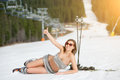 Young sexy naked skier is lying on snowy slope under ski lift at ski resort Royalty Free Stock Photo